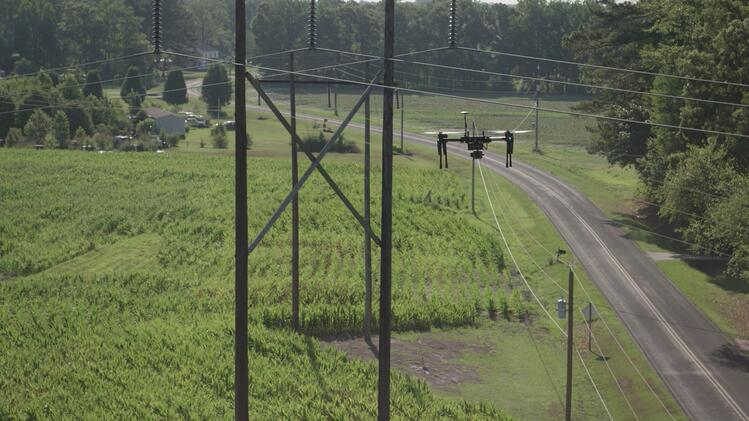 drone flying near utility pole with greenery and a road in the background