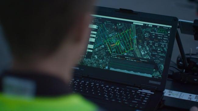 UgCs PrecisionFlight Pro on laptop over shoulder of flight ops
